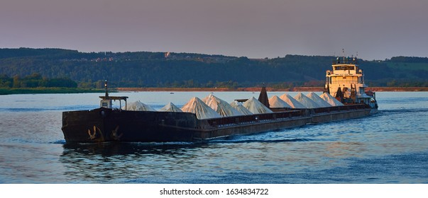 Transportation industry. Ship barge transports scrap metal and sand with gravel