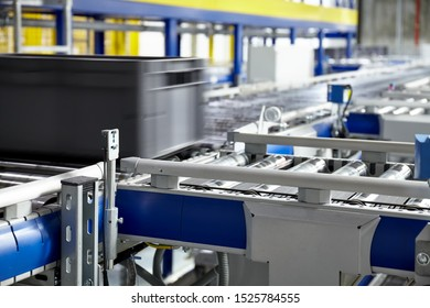 Transportation line conveyor roller with container in motion, selective focus.