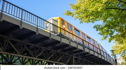 Transportation means. Yellow electric train on steel bridge, Berlin, Kreuzberg east side, Germany. Under view.
