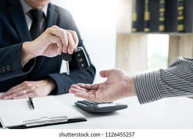 transportation and ownership concept - customer and salesman with key agent is holding the document approve car loan and insurance