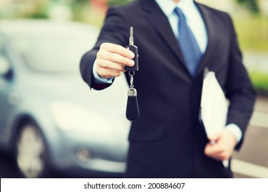 transportation and ownership concept - man with car key outside