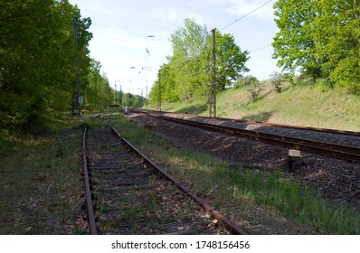 Transportation / Railway: Old and no longer used sidetrack at the edge of an electrified double-track railway line in Central Germany on a sunny day in May