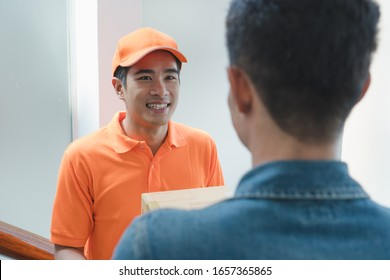 transportation same day delivery business concept. Smiled asian young delivery man send urgent package box to receiver / client on the door home with friendly attitude.