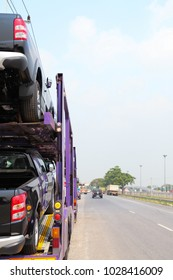 Transportation truck carry new cars on the street to local market for distribution in sunny day.