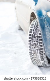 transportation, winter and vehicle concept - closeup of car winter tire