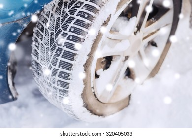 transportation, winter and vehicle concept - closeup of car wheel