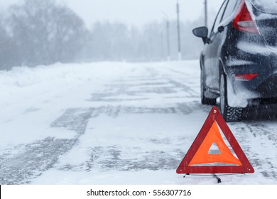 Transportation, winter and vehicle concept - closeup of red warning triangle with a broken down car