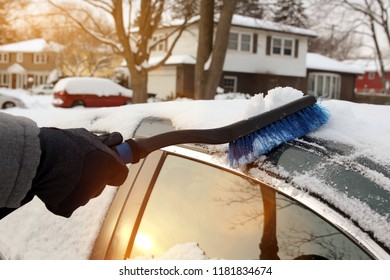 Transportation, winter  and vehicle concept - man cleaning snow from car with brush