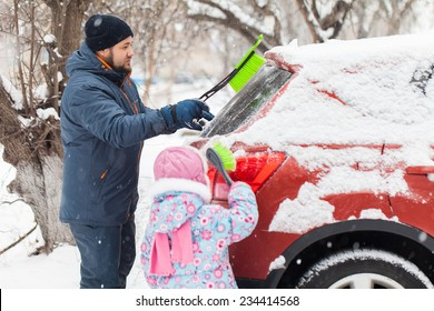 Transportation, winter, weather, people and vehicle concept - man and kid cleaning snow from car with brush