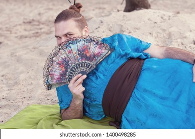 transsexual handsome man with hair bun lying on sand in blue kimono and covering face with hand fan