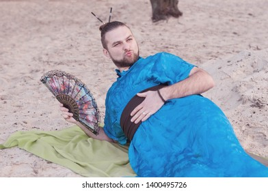 transsexual handsome man with make up, hair bun lying on sand in blue kimono, showing kissing and holding hand fan on rug