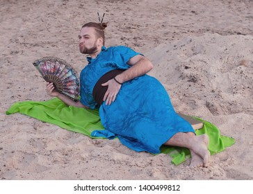 transsexual handsome man with make up, hair bun lying on sand in blue kimono, giving kiss, holding hand fan and looking away on rug
