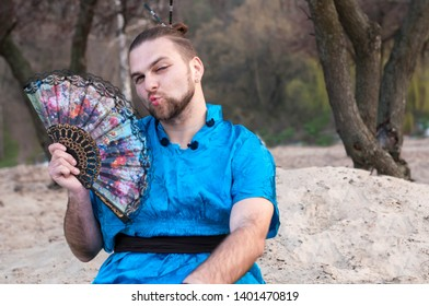 transsexual handsome man with make up, hair bun sitting on sand in blue kimono, winking, showing kissing and holding hand fan in front of trees