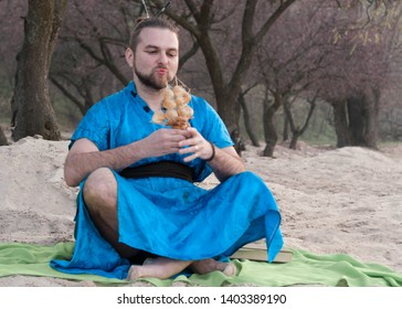 transsexual handsome man with make up, hair bun sitting on sand in blue kimono, looking at ship model with seashells in front of trees on beach
