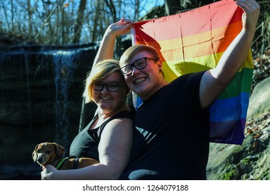 Transsexual male and lesbian woman cuddle together with their dog while holding the rainbow gay pride flag outside