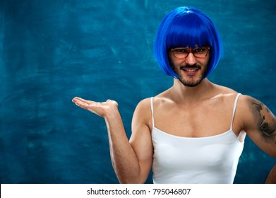 Transsexual person wearing blue wig and glasses showing something useful on blank space. Place for text