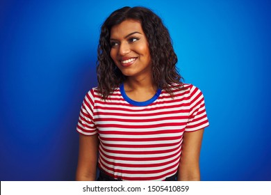 Transsexual transgender woman wearing stiped t-shirt over isolated blue background looking away to side with smile on face, natural expression. Laughing confident.