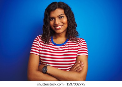 Transsexual transgender woman wearing stiped t-shirt over isolated blue background happy face smiling with crossed arms looking at the camera. Positive person.