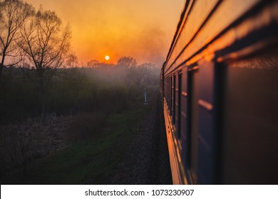 The Trans-Siberian Railway, the journey of a lifetime. Traveling by train during orange sunset. View from behind the window