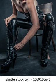 transvestite gets his knee high heel boots on closing the zipper. Woman ollusion in shiny fetish fashionable corset, leggings, pants and boots.