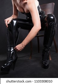 transvestite takes on her knee high heels platform boots closing the zipper. sitting on a chair. wearing black shiny rubber or pvc clothing such as a corset and trousers