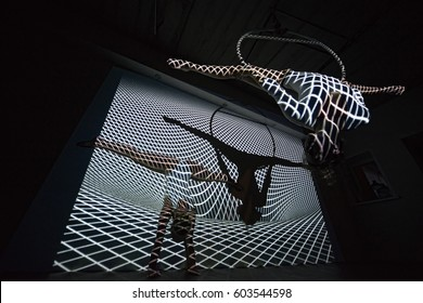 trapeze artist doing side splits in the air ring
