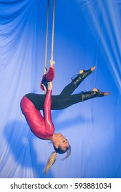 Trapeze women; Hanging from the trapeze in front of a blue background