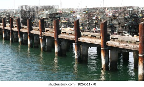 Traps, ropes and cages on pier, commercial dock, fishing industry in San Diego harbor, California USA. Empty pots and creels for seafood catching in port. Many fishermen's nets and baskets in seaport.