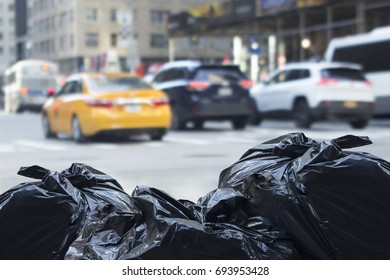 Trash bags with blurry traffic in background in urban environment with recycle concept.
