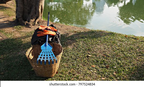 Trash bin basket , garden fork and gloves in public park. Tools for cleaning park or garden.