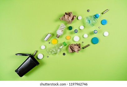 Trash bins and assorted garbage isolated on green, recycle concept, Top view