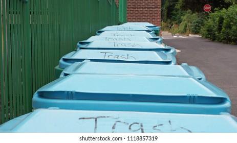 Trash bins in a row in alley
