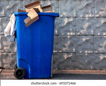 The trash can of blue color filled with a garbage at the top costs on the street near a gray stone wall.