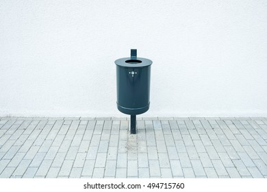Trash can in front of a white wall