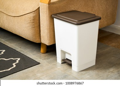 Trash can on the edge of sofa corner