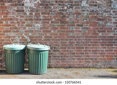 trash can rubbish bin dustbins garbage trashcan can outside against brick wall background with copy space