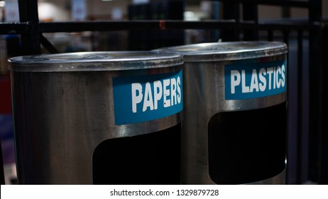 Trash cans labeled to separate plastic and papers.
