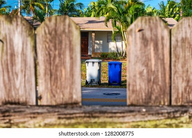 Trash cans of neighbor from the point of view of other homes fences.