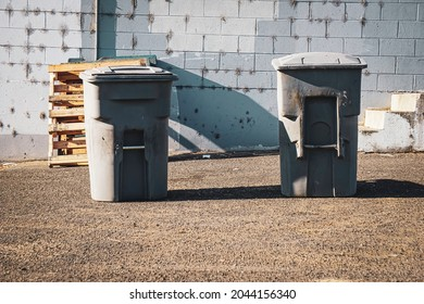 Trash cans in urban alley behind building