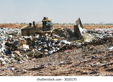 A trash compactor moves trash in a landfill. The stench is amazing!