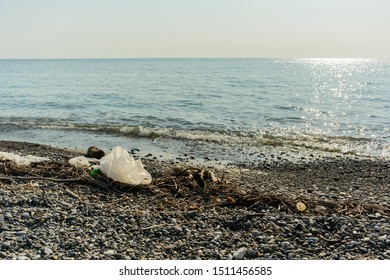 trash and junk on dirty pebble beach of Black Sea in Sochi of Russia, pollution concept, stock photo image