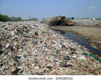 Trash mountain and waste water with trash truck and backhoe in dirty place of the city. Environment problem in urban city.