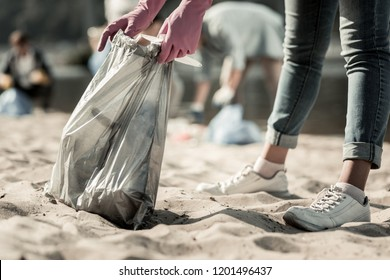 Trash on beach. Close up of young student wearing dark blue jeans and white sneakers cleaning up trash on the beach