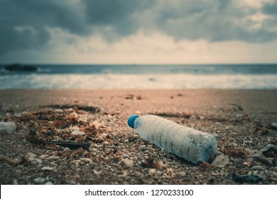 Trash, plastic, garbage, bottle... environmental pollution on the beach. Royalty high-quality free stock photo image of trash, plastic bottle on the beach. Waste that polluted the ocean environment