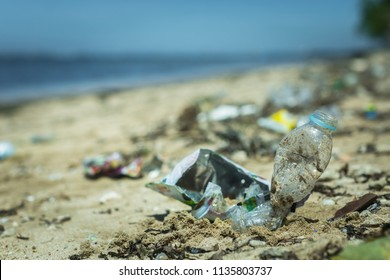 Trash and plastic lying on the beach. Plastic in the ocean. Littering.