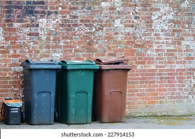 trashcan trash can rubbish bin dustbins can outside against brick wall with copy space  wheelieoutside trashwheelyrecycle background with copy space of wall stock, photo, photograph, picture, image