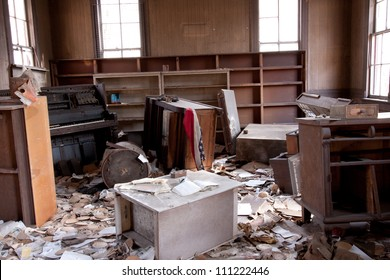 Trashed room with old furniture and papers scattered about.