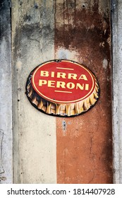 TRASTEVERE, ROME, ITALY - SEPTEMBER 12, 2020: Birra Peroni Commercial Sign. Authentic, Vintage Oval Sign of the Famous Italian Beer Placed on a Peeling Wall of a Restaurant in Piazza Saint Egidio
