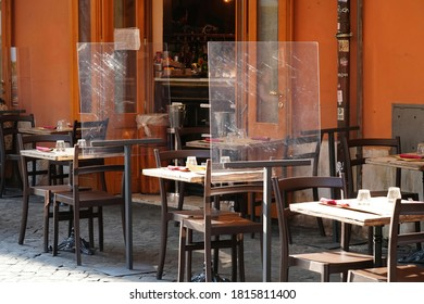 TRASTEVERE, ROME, ITALY - SEPTEMBER 12, 2020: Social Distancing and Restoration Business. Empty Tables Outside a Typical Restaurant. Pastic, Plexiglass Screens on Metal Stands for Customer Separation