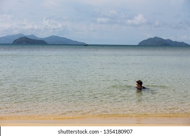 TRAT, THAILAND. APR 10, 2017: Mountain with man floating over the sea with bright sky in background in the afternoon at Koh Mak Island in Trat, Thailand.